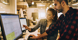Young businessman and business woman looking at computer screen of spreadsheets.