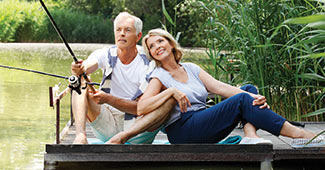 Retired couple sitting on a dock fishing and smiling.